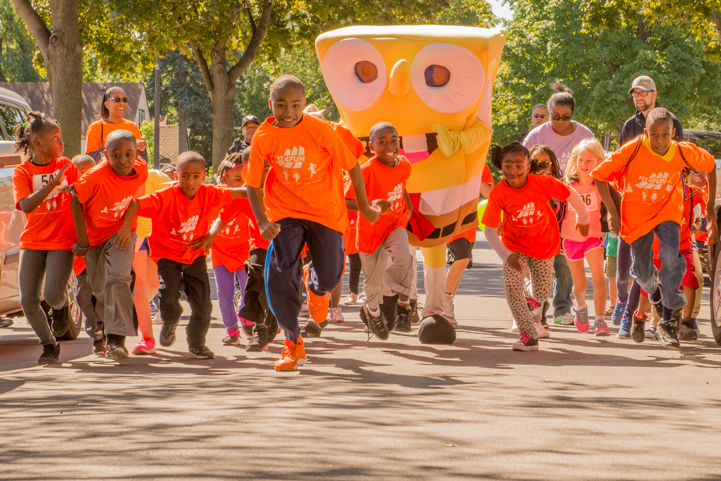 Kids running in street with mascot